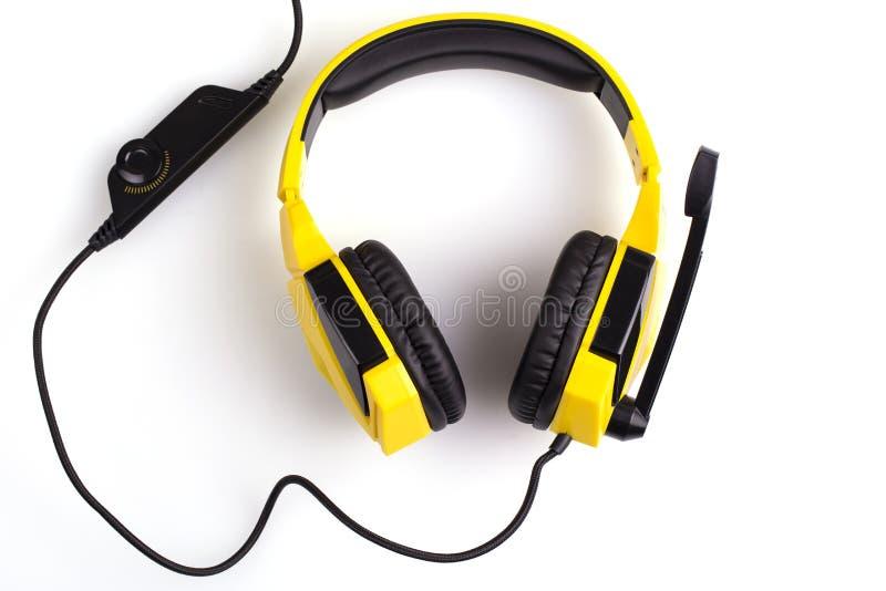 Желтые наушники с микрофоном изолированным на белой предпосылке стоковая фотография