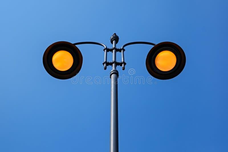 Желтые освещая поляки улицы на голубом небе стоковые фотографии rf