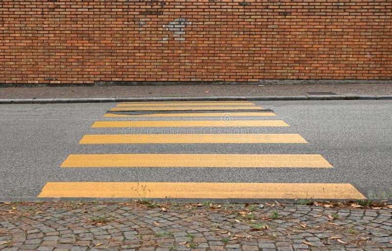 Желтые покрашенные линии дороги crosswalk на асфальте между тротуаром порфиры 2 Кирпичная стена Grunge на предпосылке стоковые изображения rf