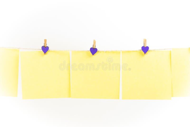 Желтые стикеры на веревке для белья с зажимками для белья изолированными на белой предпосылке стоковое фото rf