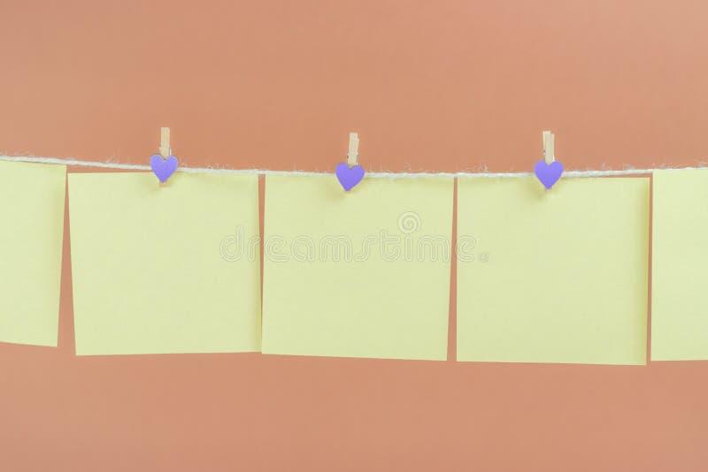 Желтые стикеры на веревке для белья с зажимками для белья изолированными на коричневой предпосылке стоковое изображение