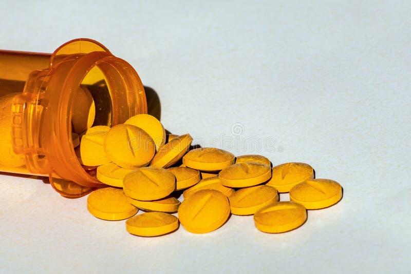 Желтые таблетки рецепта разлили на таблицу Концепция наркомании opioid и стоковое фото