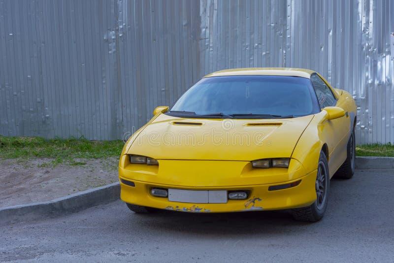 Желтый автомобиль спорт реален во дворе  жилого дома с затрапезным бампером стоковые фотографии rf