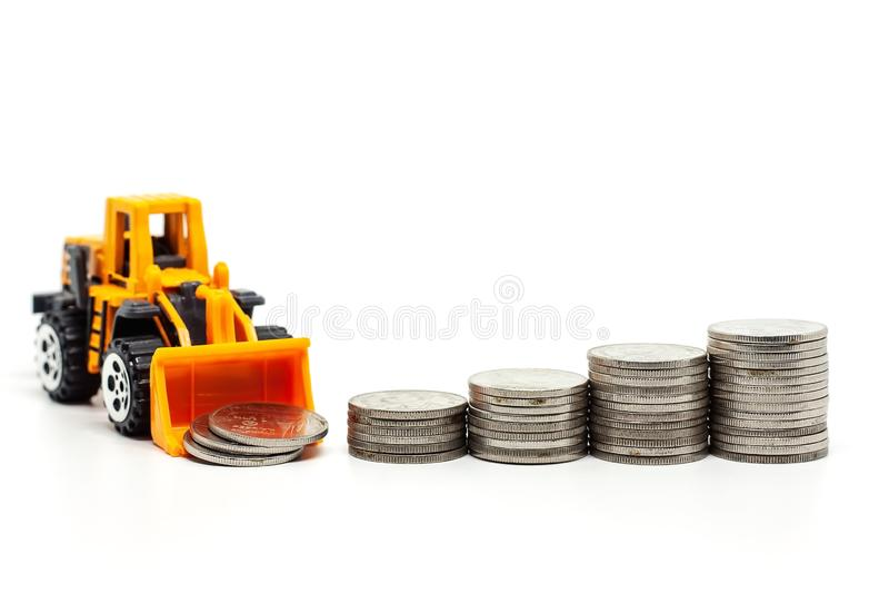 Желтый бульдозер игрушки с кучей монеток на белой предпосылке стоковая фотография