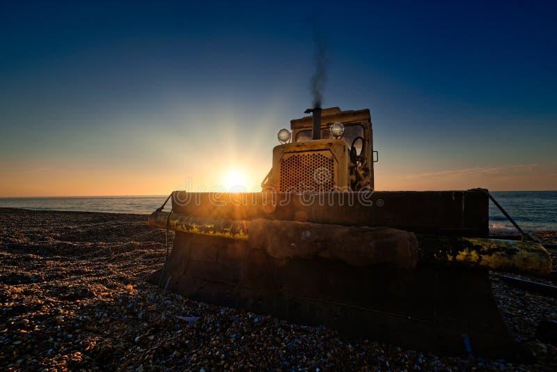Желтый бульдозер на пляже на восходе солнца стоковая фотография
