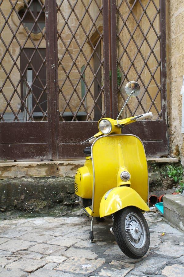 Желтый винтажный скутер припаркованный перед tipical домом в деревне Salento, Италии Один из самого популярного перехода внутри стоковое изображение