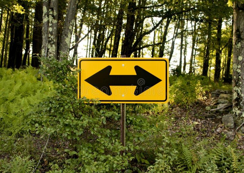 Желтый двухсторонний знак на стороне проселочной дороги в древесинах стоковые изображения