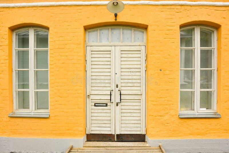желтый дом кирпича с большим Windows и деревянной дверью стоковые изображения
