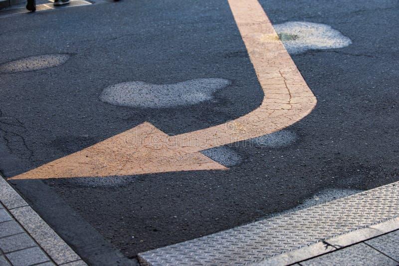 Желтый дорожный знак стрелки на влажной дороге асфальта после маленький идти дождь в центре города стоковое изображение