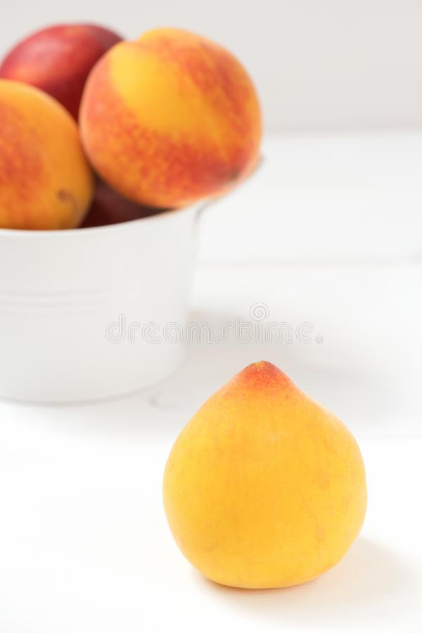 Желтый итальянский персик на белой деревянной предпосылке стоковые изображения rf