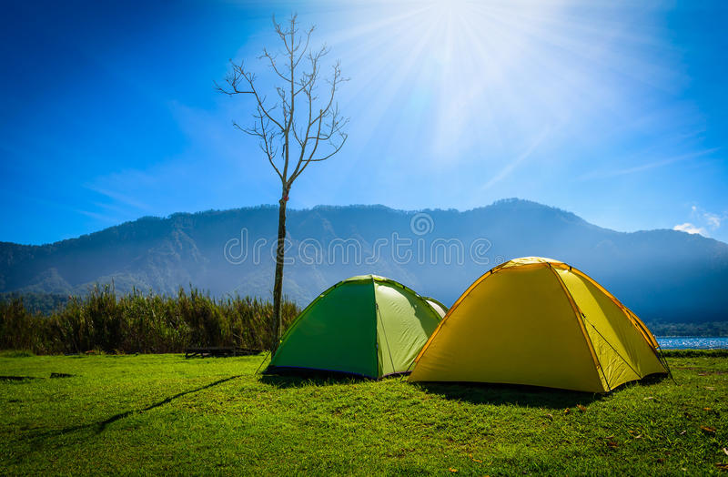 Желтый и зеленый располагаясь лагерем шатер на траве около реки горы в mo стоковое фото