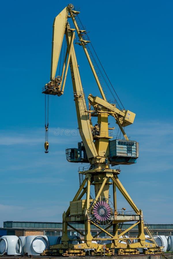 Желтый кран причала на промышленной гавани в Ростоке стоковые фото