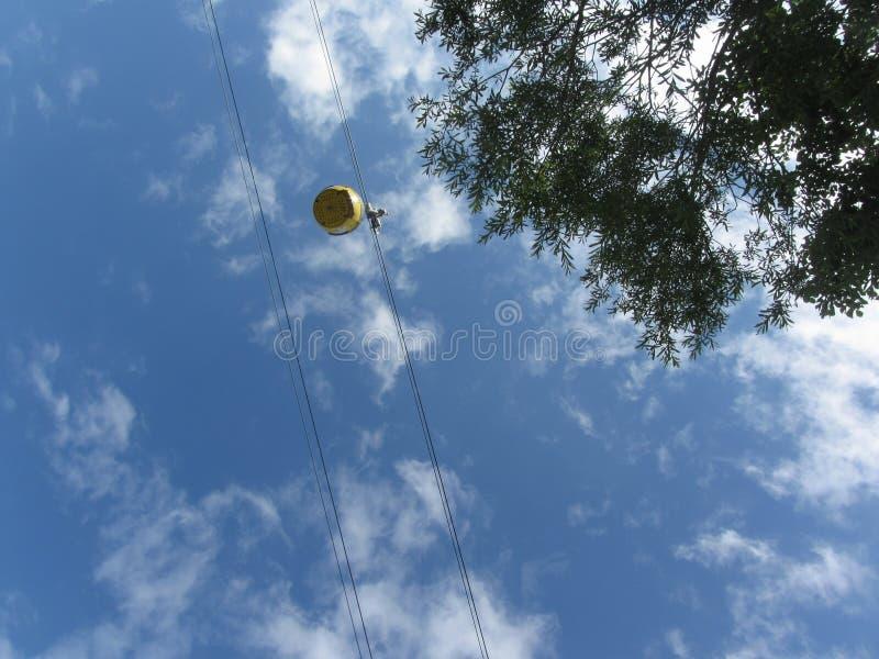 Желтый подъем кабины лыжи для движений лыжников и snowboarders в воздухе на кабел-кране Взгляд снизу на предпосылке неба стоковые изображения