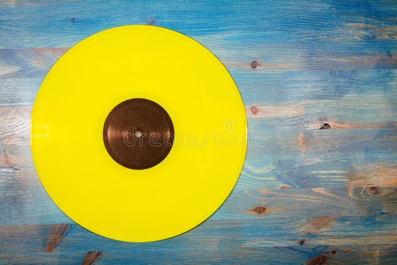 Желтый показатель винила на голубой деревянной предпосылке стоковое изображение rf