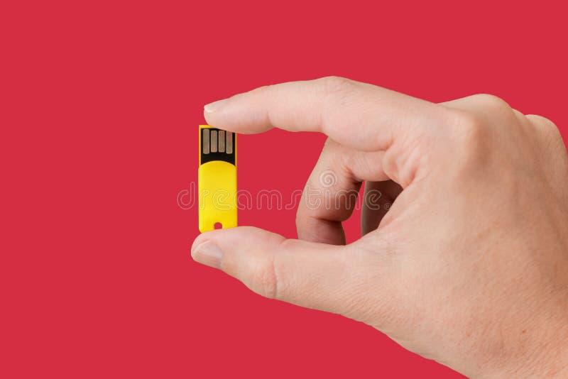 Желтый привод вспышки USB в наличии с изолированной красной предпосылкой стоковая фотография