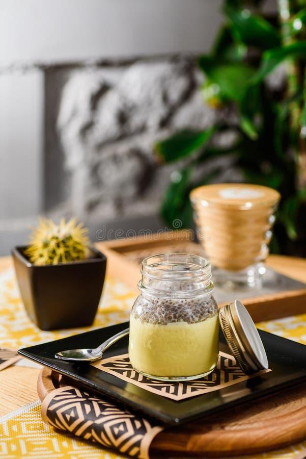 Желтый пудинг chia в опарнике на деревянном столе в ресторане Красивая сервировка пудинга chia в ресторане стоковое изображение rf