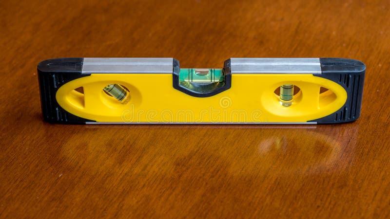 Желтый пузырь показа уровня пузыря в ровном положении для указания плоского самолета, отдыхая на коричневой деревянной поверхност стоковые изображения rf