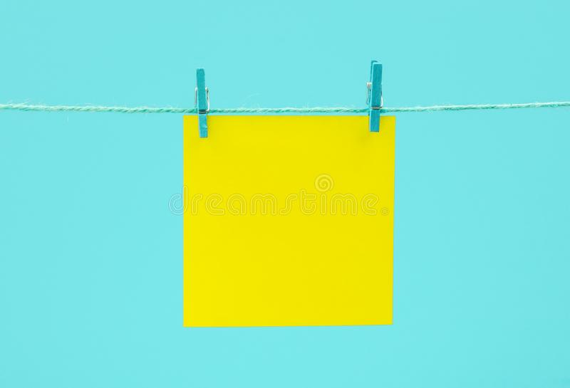 Желтый пустой бумажный лист на строке с зажимками для белья против голубой предпосылки стоковое фото rf
