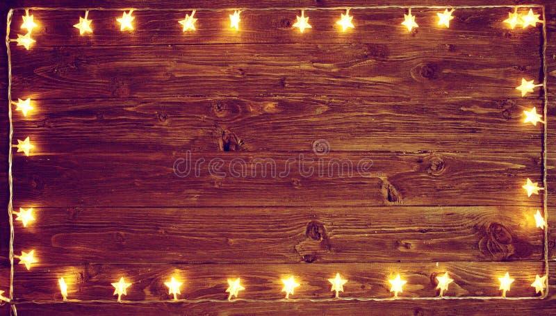 Желтый свет рождества над деревенской деревянной предпосылкой Концепция рождества или Нового Года тонизированное изображение стоковое фото rf