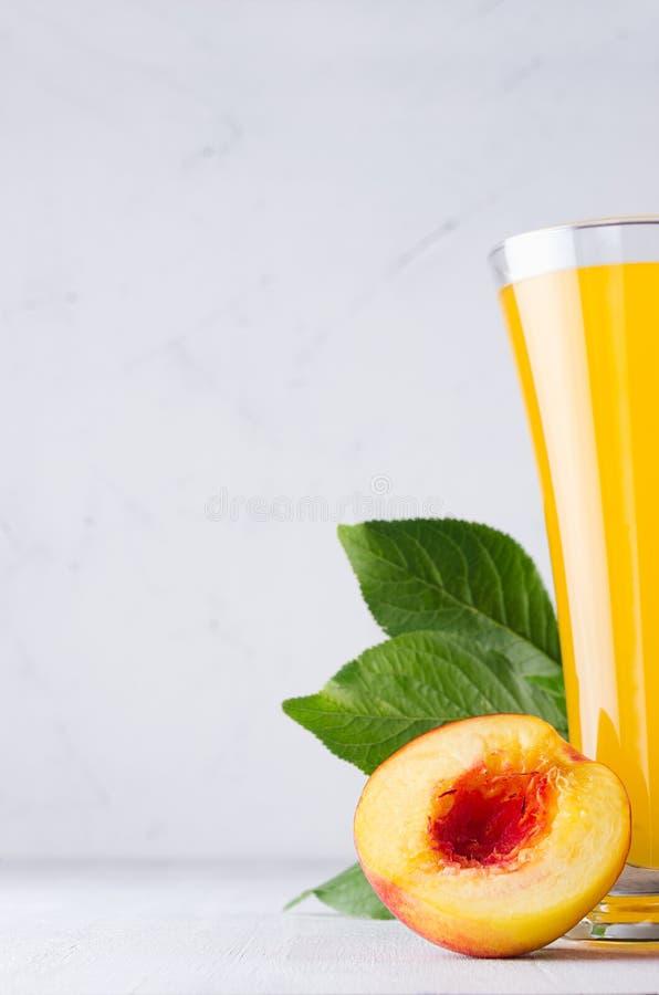 Желтый сок персика и красный нектарин половинные с предпосылкой мягкого света крупного плана листьев зеленого цвета белой деревян стоковое изображение rf