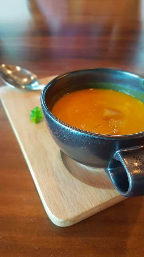 Желтый суп тыквы в черных чашках супа стоковое изображение