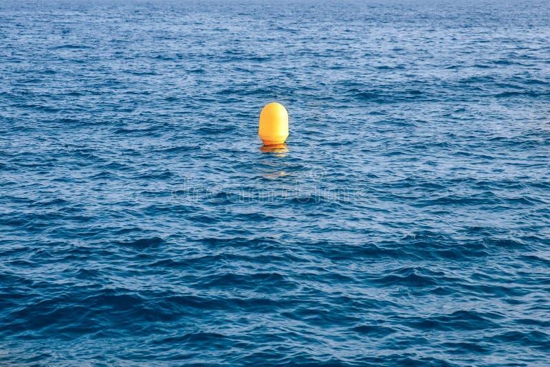 Желтый томбуй на предпосылке голубого моря, одиночестве концепции стоковые фото