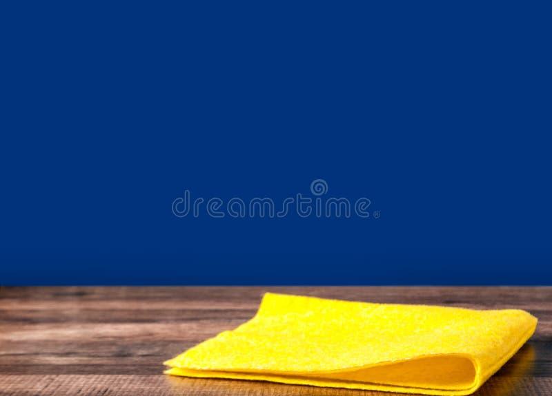 Желтый цвет салфетки на предпосылке кухонного стола голубой стоковые изображения rf
