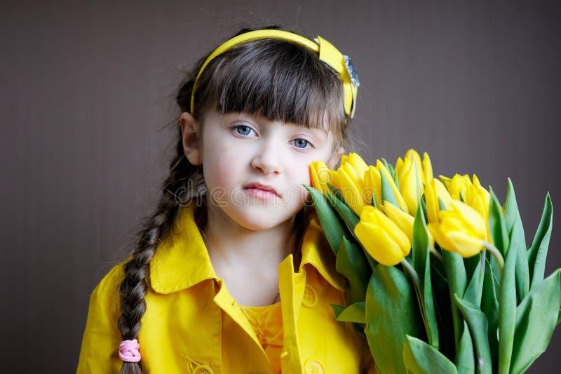 желтый цвет тюльпанов девушки ребенка букета солнечный стоковое изображение