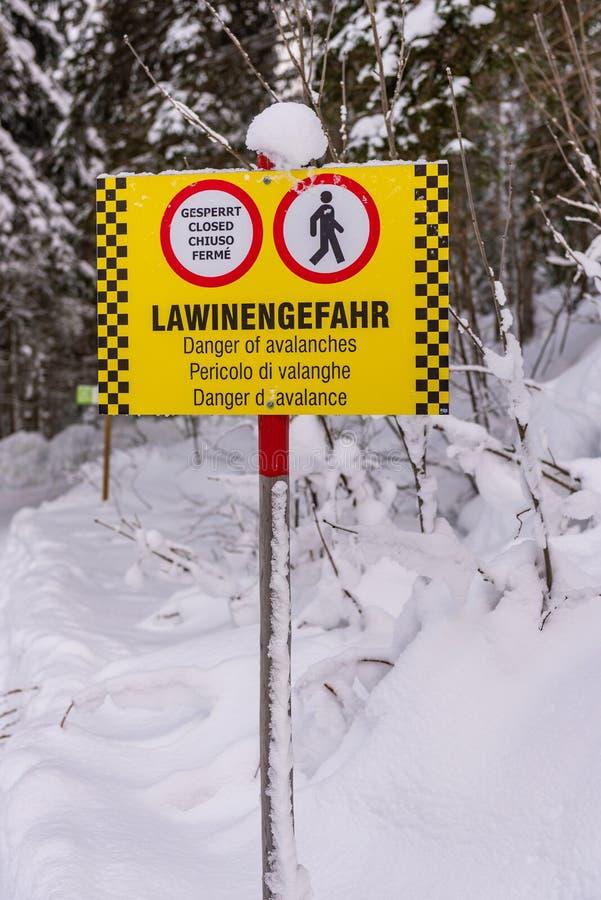 Желтый черный предупреждающий знак и знаки на немецком, английском, итальянском и французском языках: Закрыто, угроза лавины Снеж стоковое фото rf