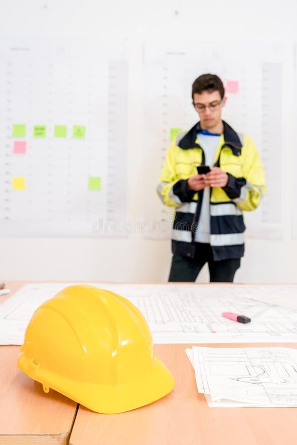 Желтый шлем на таблице с подрядчиком используя телефон в офисе стоковое изображение
