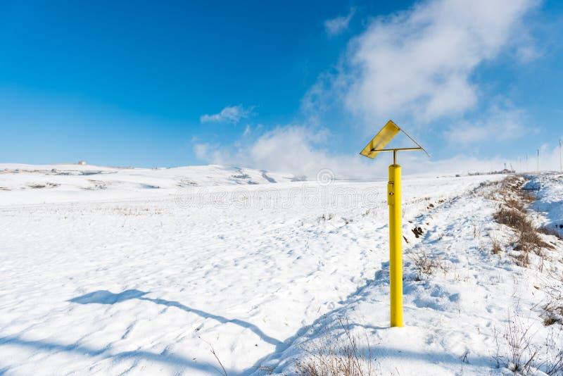 Желтый штендер, указатель газа на наклоне снежной горы стоковое фото