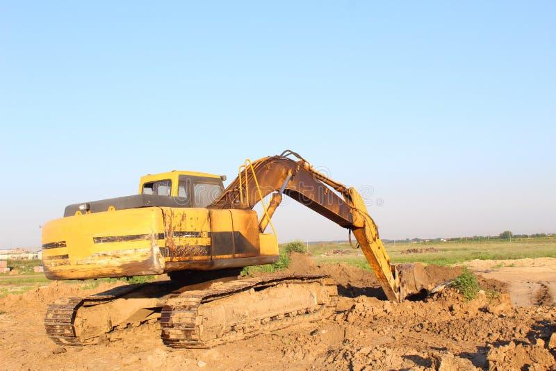 Желтый экскаватор копая экскаватором стоковое изображение rf