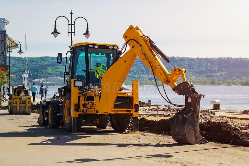 Желтый экскаватор с пониженным ведром стоит на месте работы строительства дорог в морском порте на солнечный летний день стоковая фотография rf