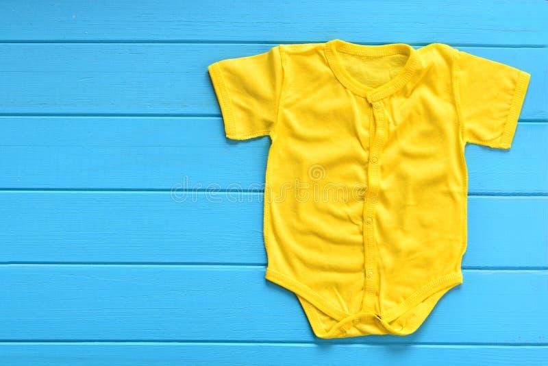 Желтый bodysuit младенца на голубой деревянной предпосылке стоковые фотографии rf