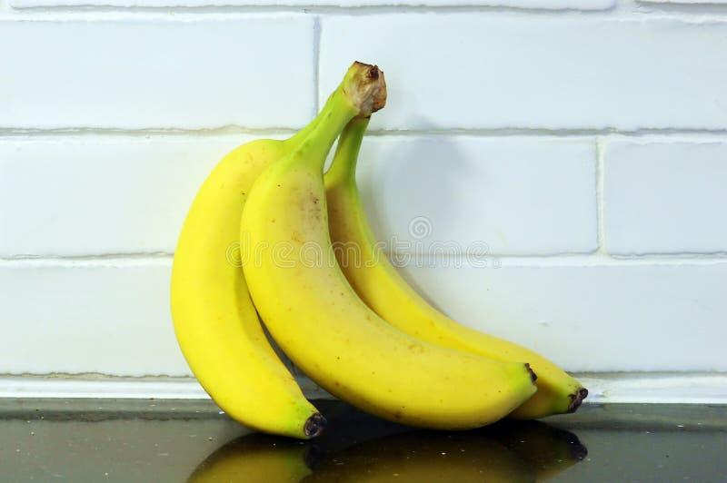 3 желтых банана на белой стене стоковые фотографии rf