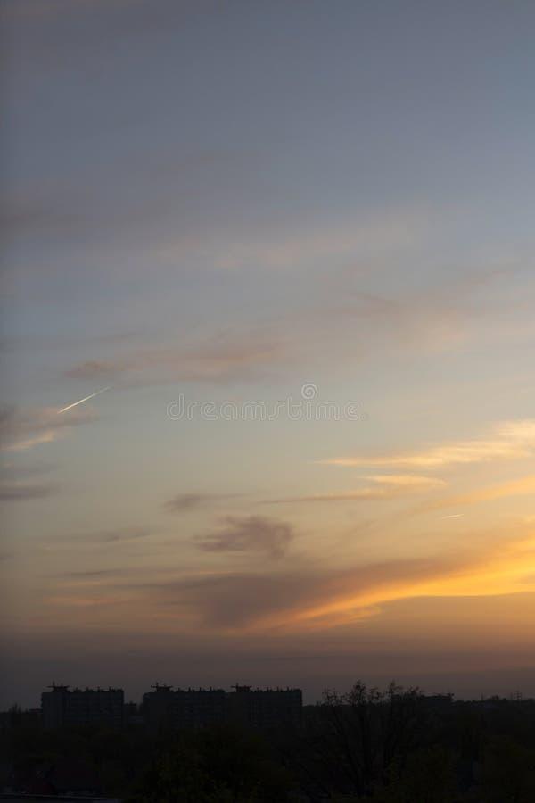 Желт-голубой заход солнца на предпосылке темного города стоковые изображения