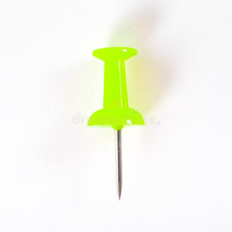 Желт-зеленый штырь нажима в белых предпосылке или обоях стоковое изображение