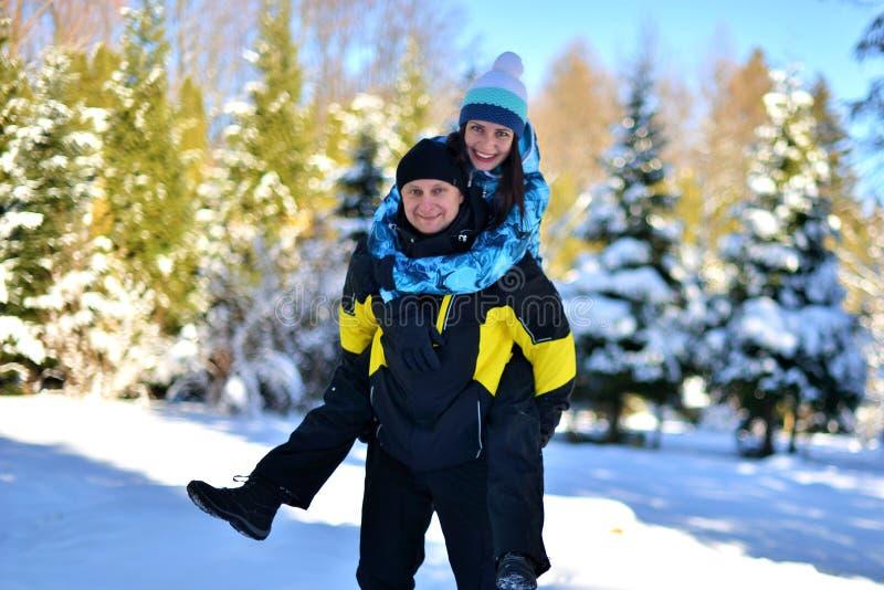 Женатая любящая пара околпачивая вокруг в снежном лесе на солнечной зиме стоковые изображения rf