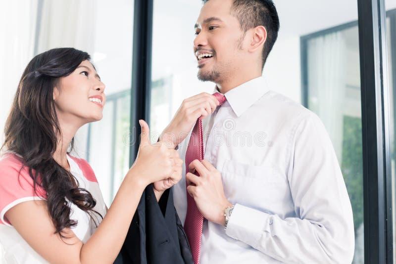 Жена помогая ее человеку идя к офису для работы стоковое изображение rf