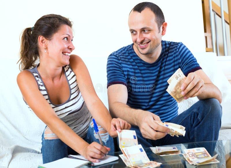 Жена прося усмехаясь деньги человека ходить по магазинам стоковая фотография