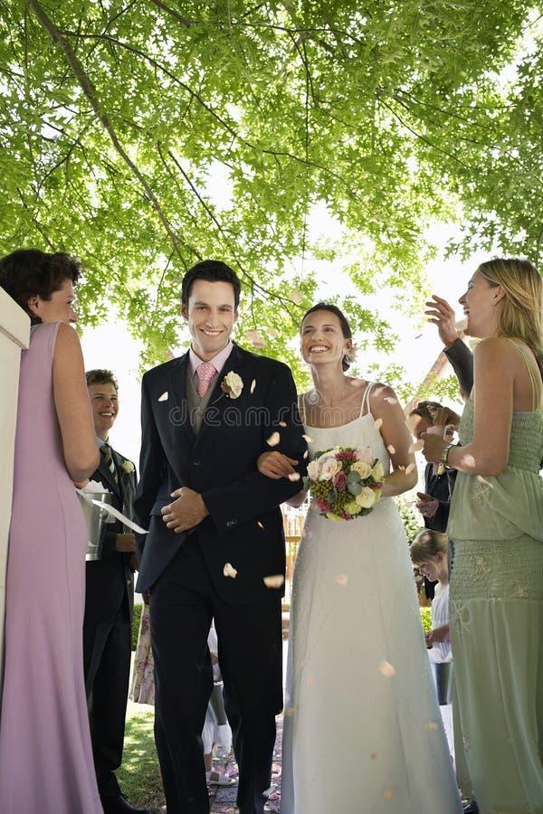 Жених и невеста будучи поливанным с лепестками цветка стоковое фото