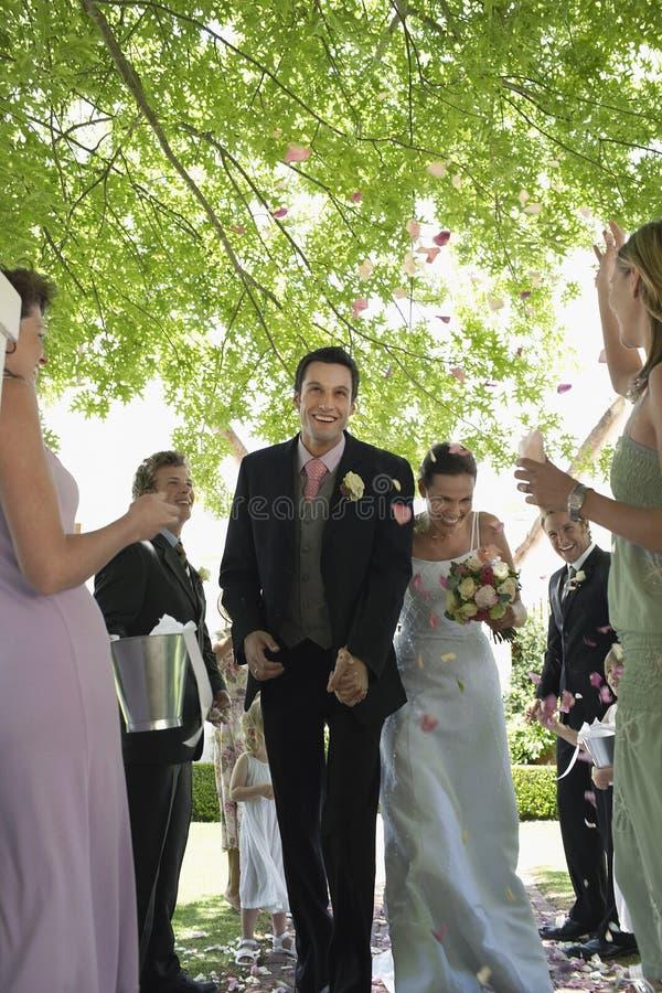 Жених и невеста будучи поливанным с лепестками цветка стоковая фотография