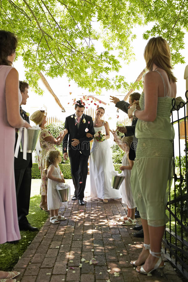 Жених и невеста будучи поливанным с лепестками цветка стоковое фото rf