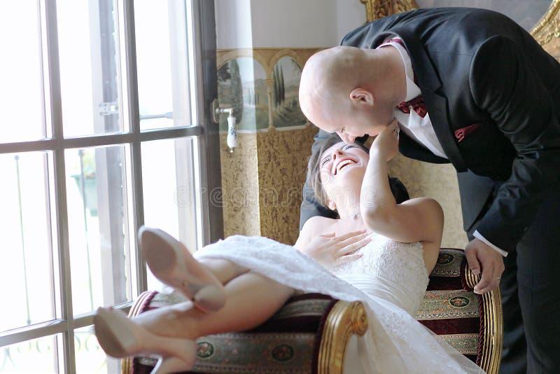 Жених и невеста в их дне свадьбы чувствуя большой стоковое изображение