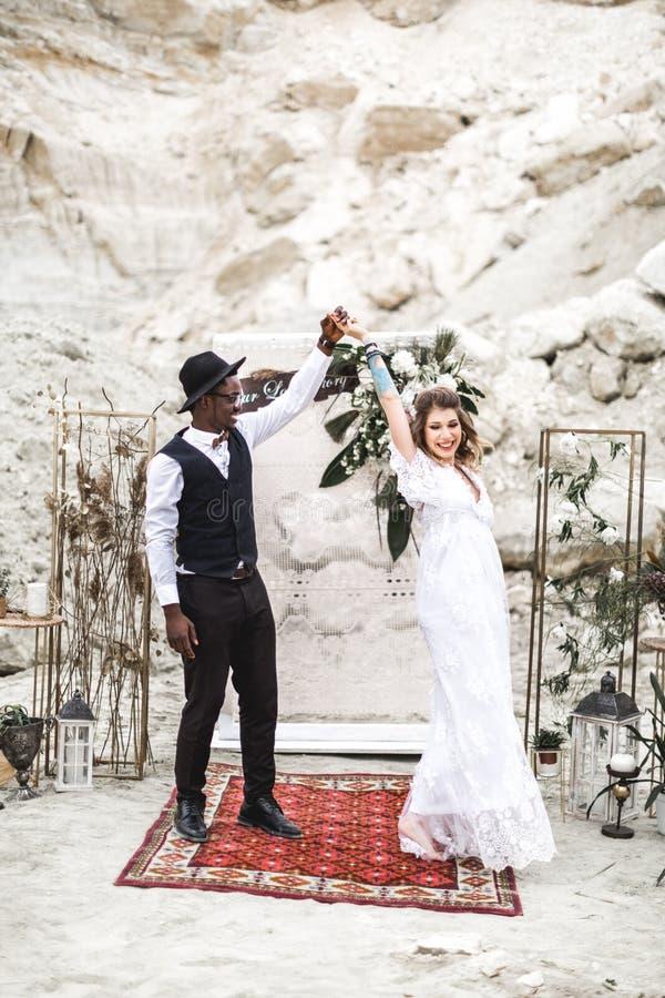 Жених и невеста в каньоне outdoors свадебная церемония свод свадьбы boho Африканский человек и кавказская женщина в носке boho стоковое изображение rf