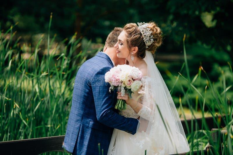 Жених и невеста в конце концов встречал после длинного разъединения и обнял в саде Сегодня день их свадьбы стоковое изображение