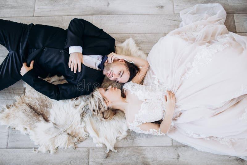 Жених и невеста в одеждах свадьбы лежит на поле и усмехаться стоковое фото rf