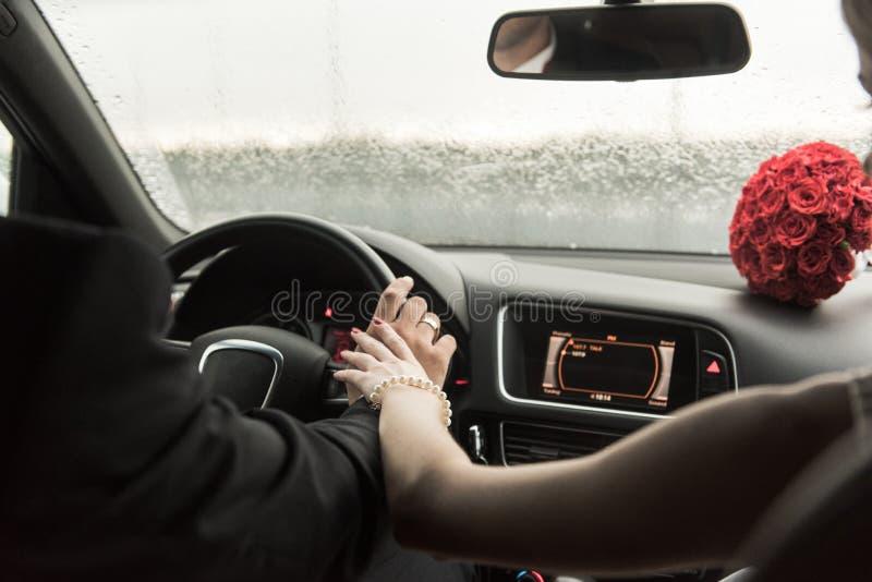Жених и невеста в дожде предусматриванном в автомобиле стоковые изображения