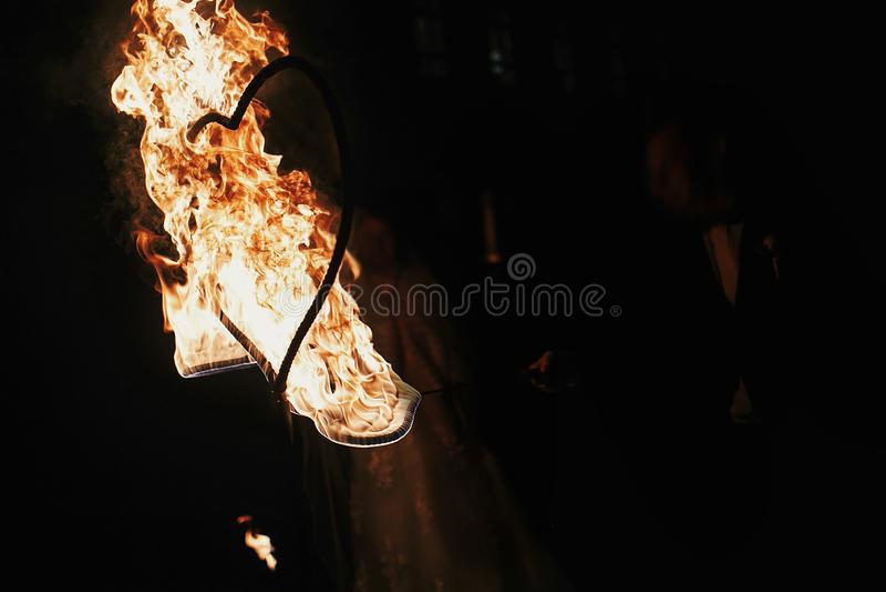 Жених и невеста держа горящие сердца, изумительную выставку огня на nig стоковое фото