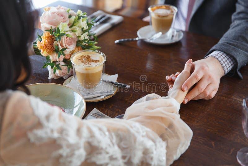 Жених и невеста держа руки в ресторане стоковое фото
